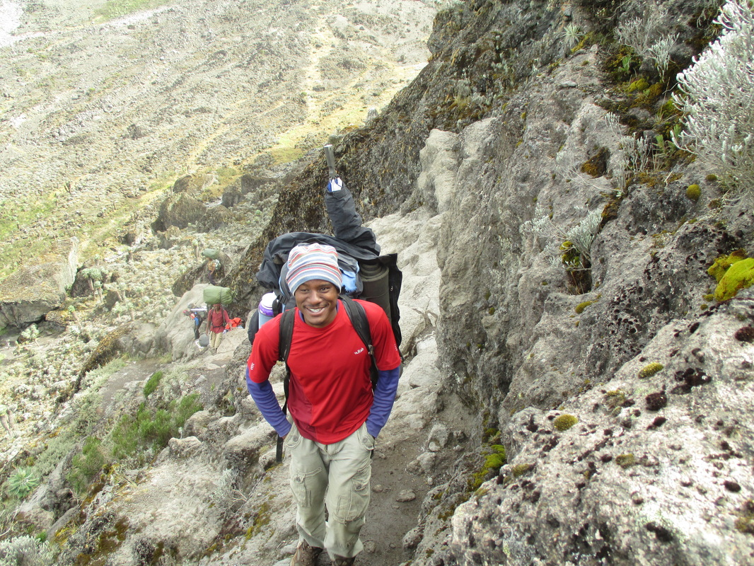A Kilimanjaro guide, making his way up Kilimanjaro's Barranco Wall.  Climb Kilimanjaro with Samba Treks, a social enterprise.